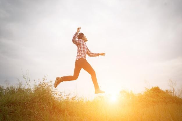 Hipster человек прыгать высоко вверх, свобода наслаждаться с природой aroun