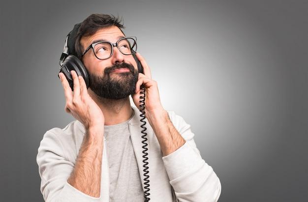 Hipster man listening music on grey background