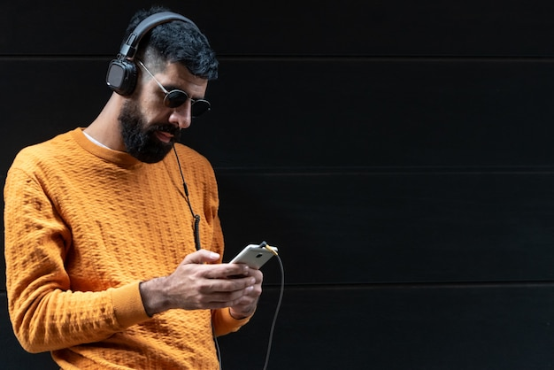 Hipster man listening music on headphones