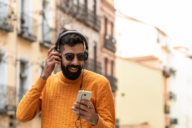 Hipster man listening music on headphones.