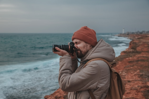 The hipster man looking to lighthouse in seaside