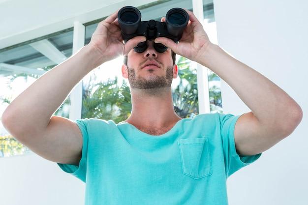 Hipster man looking through binoculars at home