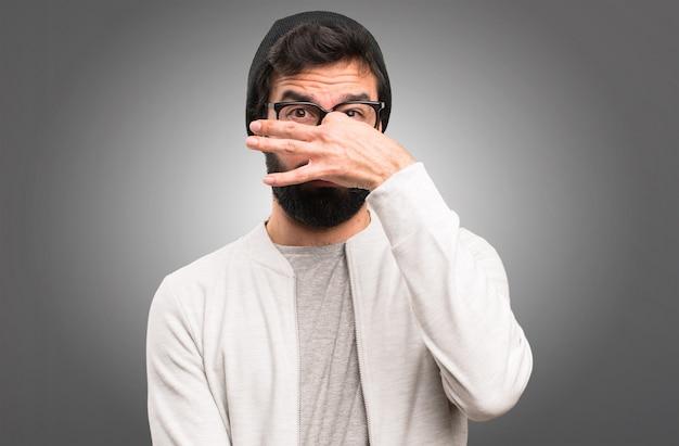 Hipster man making smelling bad gesture on grey background