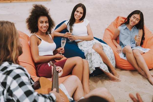 Hipster man playing guitar on beach girls smiling