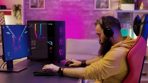 화려한 네온으로 방에서 전문 비디오 게임을 하는 힙스터 남자. 비디오 게임을 하는 동안 헤드폰을 끼고 있는 남자.