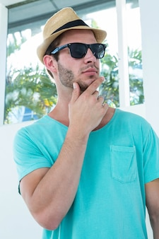 Hipster man posing with sunglasses at home