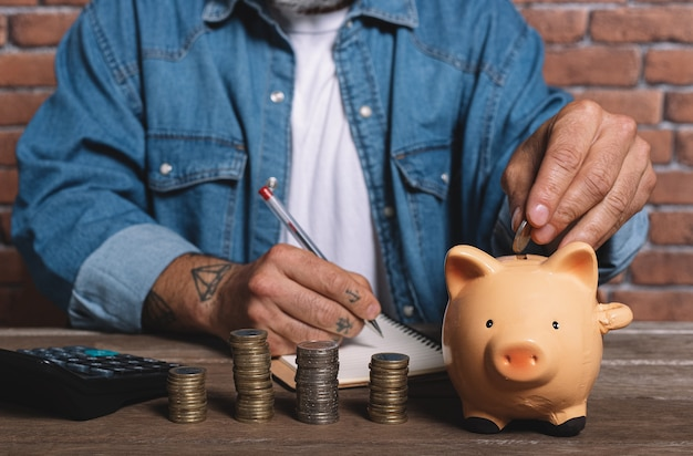 Hipster man putting coin into pig piggy bank with pile of coins on table to save money.