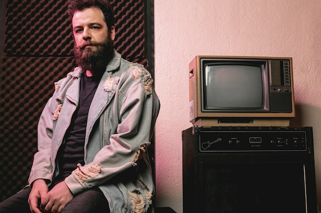 Hipster man siting next to vintage tv