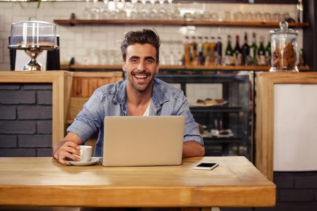 Hipster man smiling while using laptop