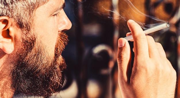 Хипстерский мужчина курит. курящий мужчина, выкуриваю сигару. курящий мужчина с бородой. бородатый мужчина с сигарой. бородатый мужчина и усы курят сигару. тлеющие сигары.