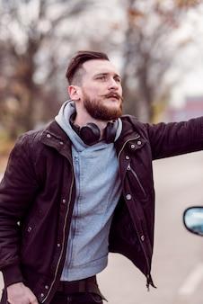 車の隣に立っている流行に敏感な男