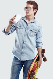 Hipster man in sunglasses and jeans jacket posing with skateboard and coffee