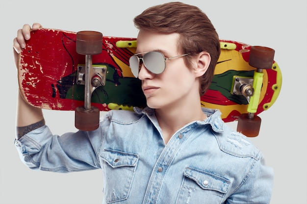 Hipster man in sunglasses and jeans jacket posing with skateboard