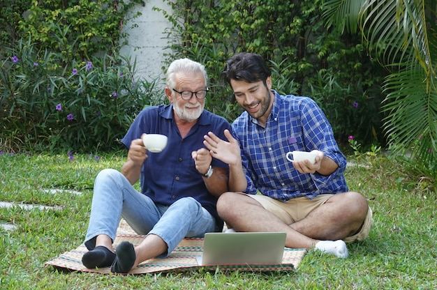 Hipster man taking care about his elderly father in house at garden.