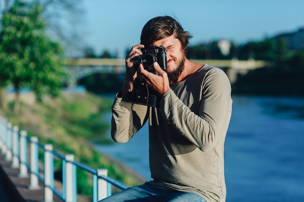 Hipster man taking a photo on retro camera outdoor