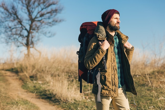 Uomo di hipster che viaggia con lo zaino nella foresta di autunno che indossa giacca calda, cappello, turista attivo, esplorando la natura nella stagione fredda