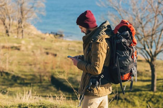 Uomo hipster che viaggia con lo zaino che indossa una giacca calda e un cappello
