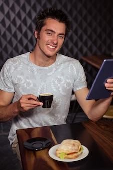 Hipster man using tablet with coffee and sandwich