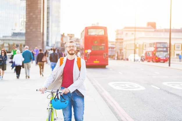 Hipster man walking on london bridge and holding his fixed gear bike