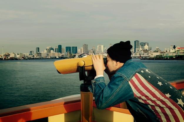都市の建物に対して双眼鏡レンズを通して見るアメリカの国旗のジーンズのジャケットを着ている流行に敏感な男