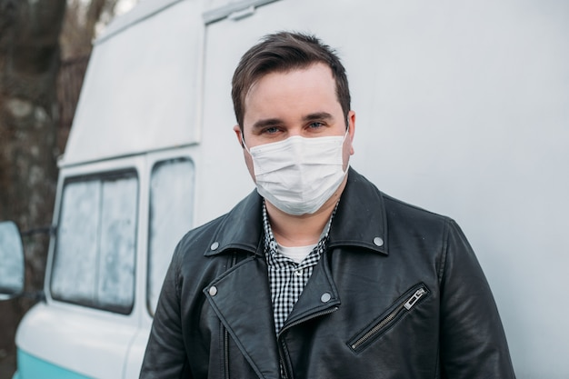 Hipster man wearing medical mask on cute retro car