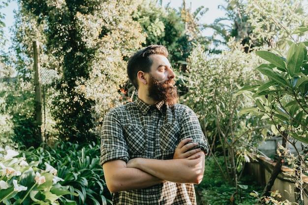 Хипстерский мужчина с бородой, скрещивающей руку посреди сада в солнечный день, концепция садоводства и свободы