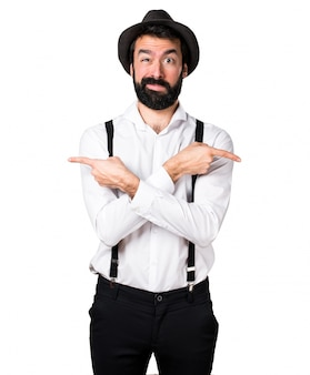 Hipster man with beard pointing to the laterals having doubts