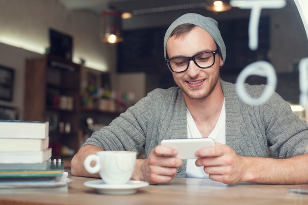 Uomo di hipster con telefono cellulare al caffè