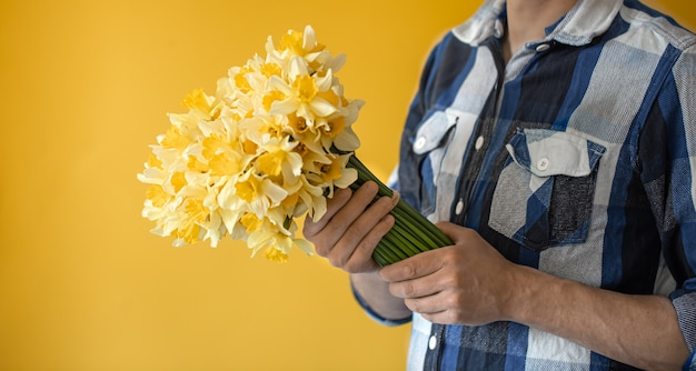Hipster man on a yellow wall in a shirt and a bouquet of flowers.