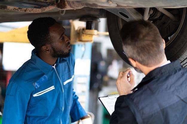 ひげとチェックリストクリップボードを持った流行に敏感な飼い葉桶が、自動車整備所の車両の下で働く専門家の整備士に話しかけます。カーケアと自動車サービスガレージのコンセプト。