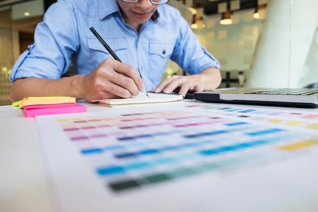 Hipster современный графический дизайнер, рисование рабочий дом, используя ноутбук в офисе.