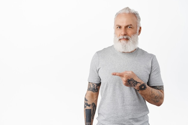 Hipster old guy with long beard showing advertisement and smiling pleased, recommending company, standing over white wall