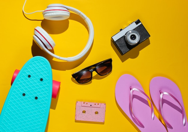 Hipster outfit. skateboard, audio cassette, headphones, flip flop, retro camera, sunglasses on yellow background.