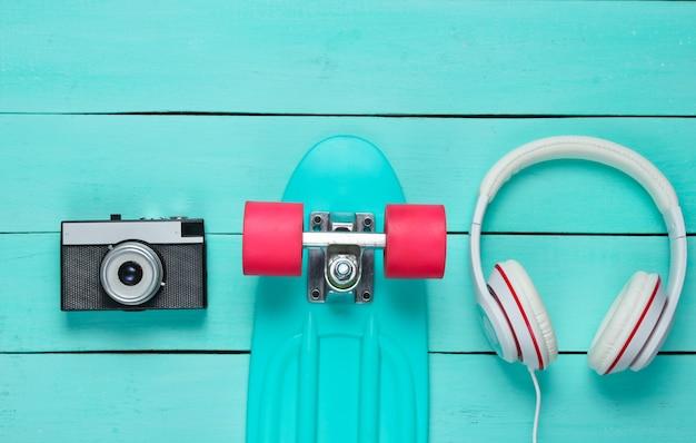 Хипстерский наряд. скейтборд, наушники, кроссовки, ретро фотоаппарат на синем деревянном фоне. креативный модный минимализм. минимальное летнее развлечение. поп-арт.