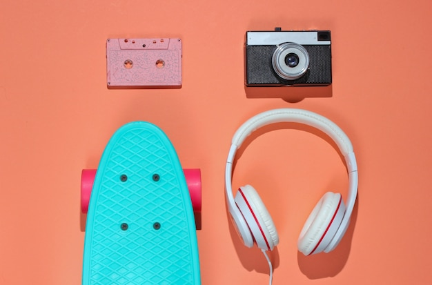 Хипстерский наряд. скейтборд с наушниками, аудиокассета на фоне кораллового цвета. креативный модный минимализм. модный ретро стиль 80-х. минимальное летнее развлечение.