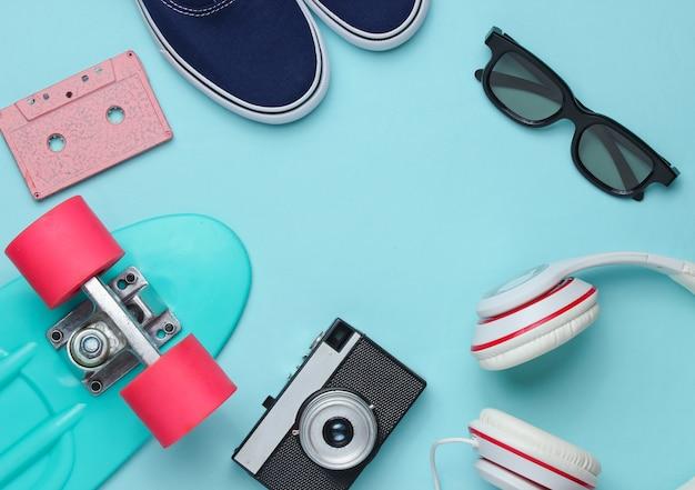 Хипстерский наряд. скейтборд с наушниками, аудиокассетой, ретро камерой и кроссовками на синем фоне. креативный модный минимализм. минимальное летнее развлечение.