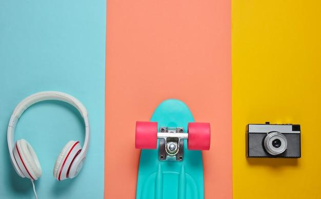 Хипстерский наряд. скейтборд с наушниками, ретро камера на цветном фоне. креативный модный минимализм. модный старомодный стиль. минимальное летнее развлечение. музыкальная концепция.