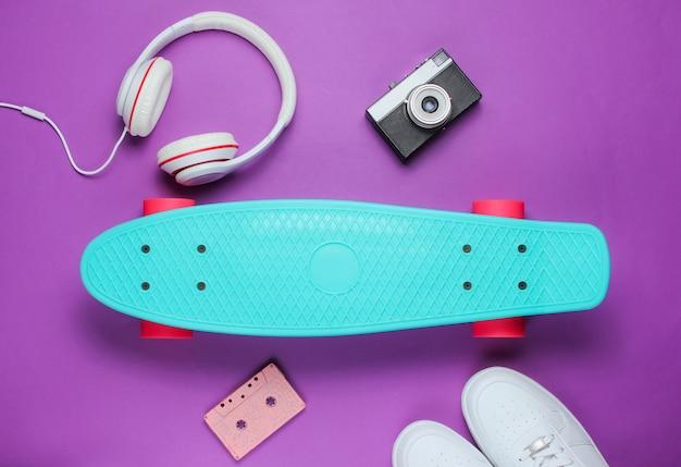 流行に敏感な服。ヘッドフォン、スニーカー、レトロなカメラ、紫色の背景にオーディオカセット付きのスケートボード。