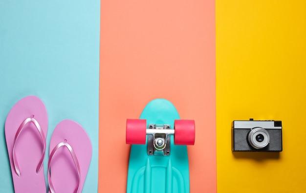 流行に敏感な服。レトロなカメラ付きのスケートボード、色付きの背景にビーチサンダル。クリエイティブなファッションのミニマリズム。トレンディな古いファッショナブルなスタイル。最小限の夏の楽しみ。音楽のコンセプト。