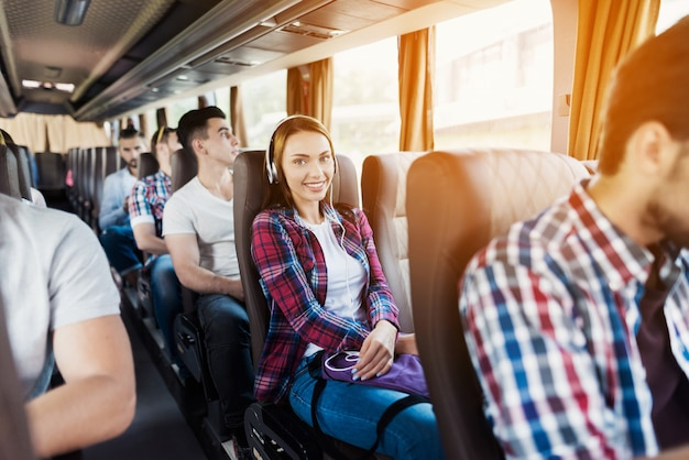 Hipster passengers have music read in travel bus.