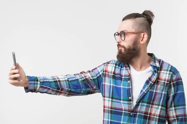 Битник, люди концепции. молодой хипстер с бородой в очках, делающий селфи