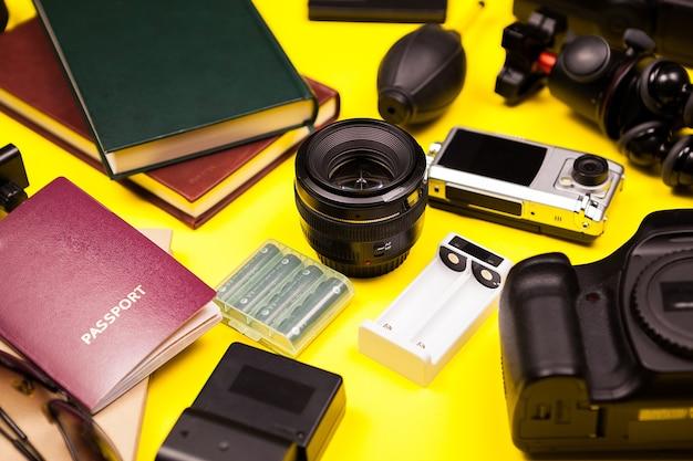 デジタル一眼レフカメラと他のアクセサリーで作られた黄色の背景に流行に敏感な写真家ブロガーキット