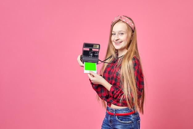 レトロなカメラを使用して写真を作る流行に敏感な写真家の若い女性。カメラに微笑んでインスタントカメラを持つ面白い女の子。ポラロイド。