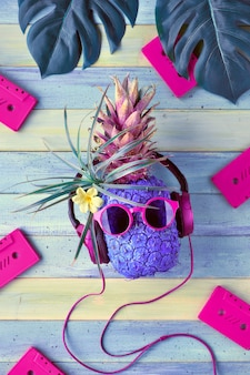 Hipster pineapple character in pink sunglasses and earphones