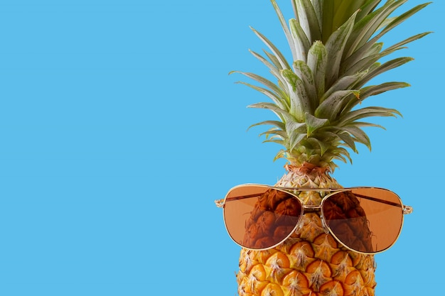 Hipster pineapple fashion accessories and fruits on blue background