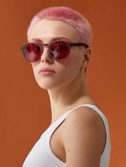 赤いサングラスの流行に敏感なピンクヘッドの女の子