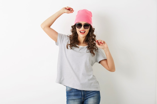 ピンクの帽子、サングラス、幸せな笑顔、長い髪、前向きな気分、感情的なヒップスターのスタイルの服、夏のファッションのトレンド、ジーンズ、ストライプのtシャツ、分離で踊るヒップスターのきれいな女性