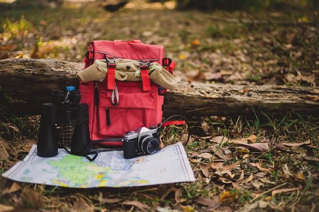 Hipster 빨간 배낭과 숲에서지도
