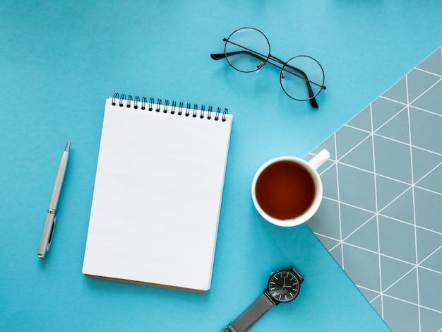 ヒップスターのやることリストのモックアップ。ノートブック、メガネ、お茶、時計を備えた創造的なデザインのテーブル。スペース色の背景をコピーします。上面図。