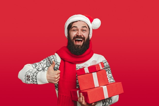 Hipster in santa hat carrying stack of presents